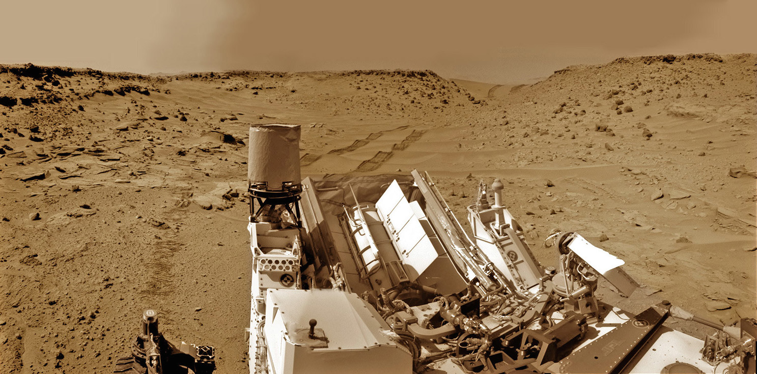 Curiosity looks back eastward to 'Dingo Gap' sand dune inside Gale Crater. After crossing over the dune on Feb. 9, 2014 the rover drove into the 'Moonlight Valley'. The parallel rover wheel tracks are 9 feet (2.7 meters) apart. Image: NASA/JPL/Ken Kremer/Marco Di Lorenzo