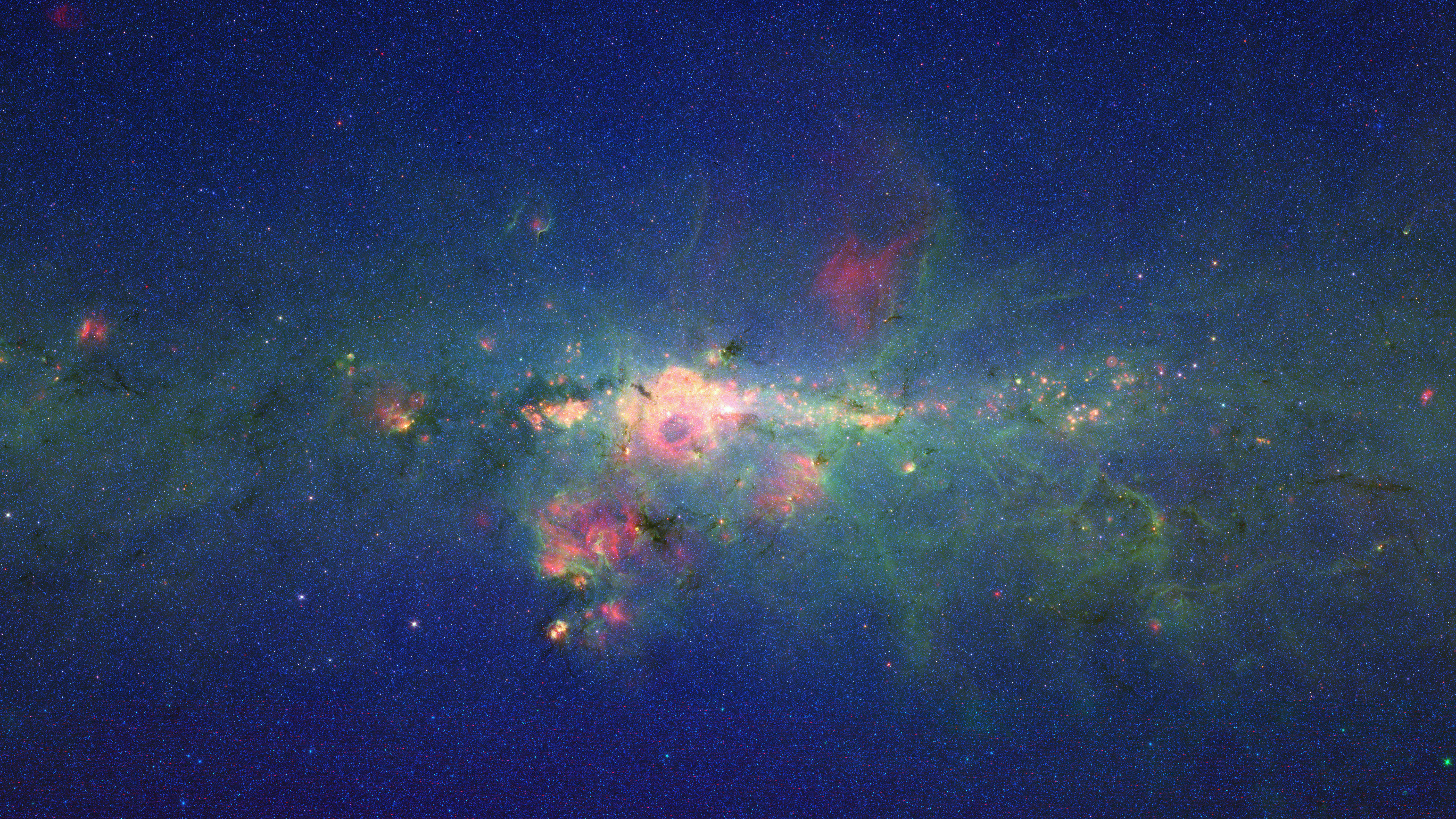 Stars Gather in 'Downtown' Milky Way: The region around the center of our Milky Way galaxy glows colorfully in this new version of an image taken by the Spitzer Space Telescope. The image is displayed (left picture) on a quarter-of-a-billion-pixel, high-definition 23-foot-wide (7-meter) LCD science visualization screen at NASA's Ames Research Center in Moffett Field, Calif. Credit: NASA/Ames/JPL-Caltech