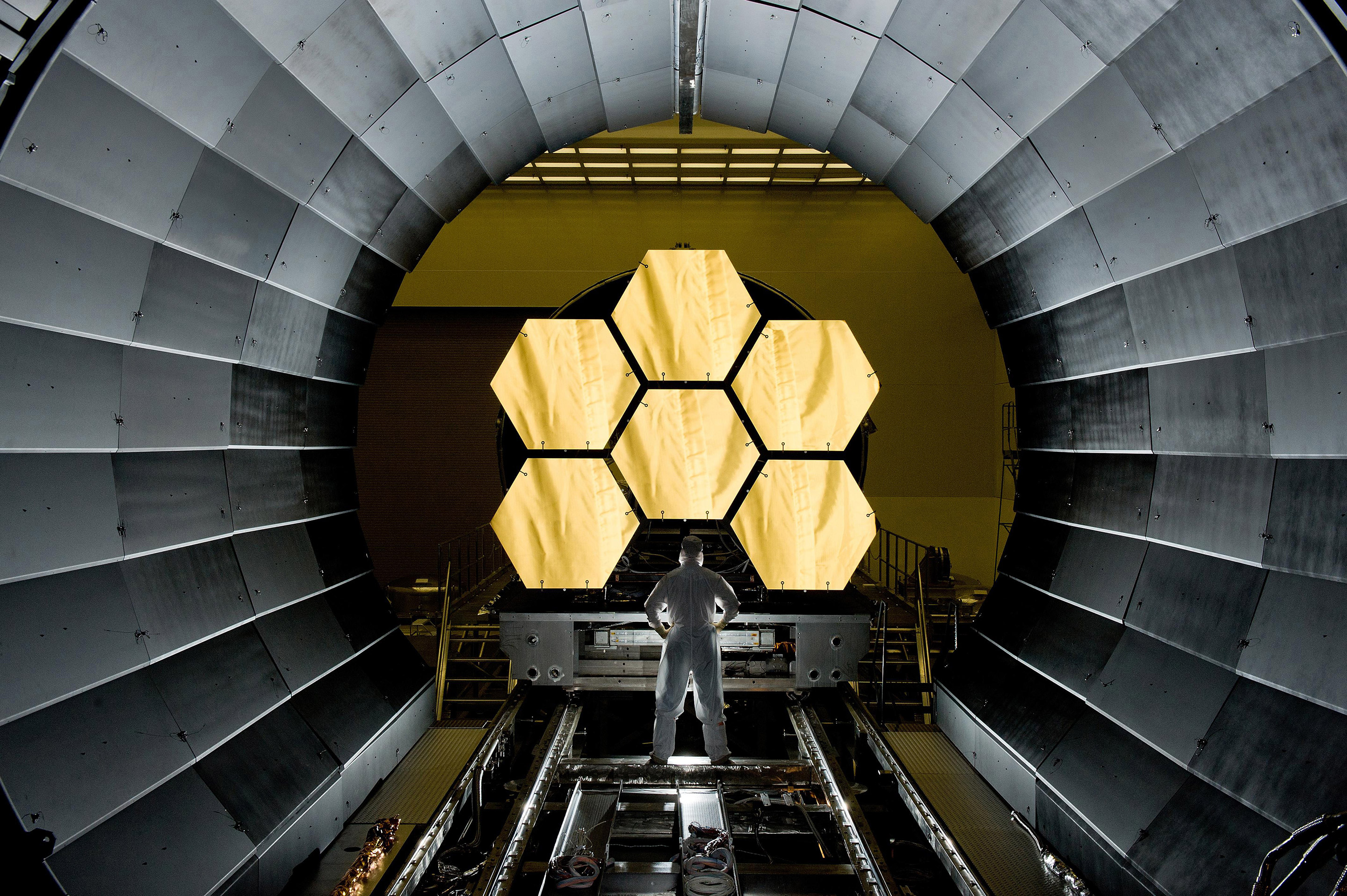 NASA engineer Ernie Wright looks on as the first six flight ready James Webb Space Telescope's primary mirror segments are prepped to begin final cryogenic testing at NASA's Marshall Space Flight Center. This represents the first six of 18 segments that will form the telescope's primary mirror. Photo: NASA/MSFC/David Higginbotham