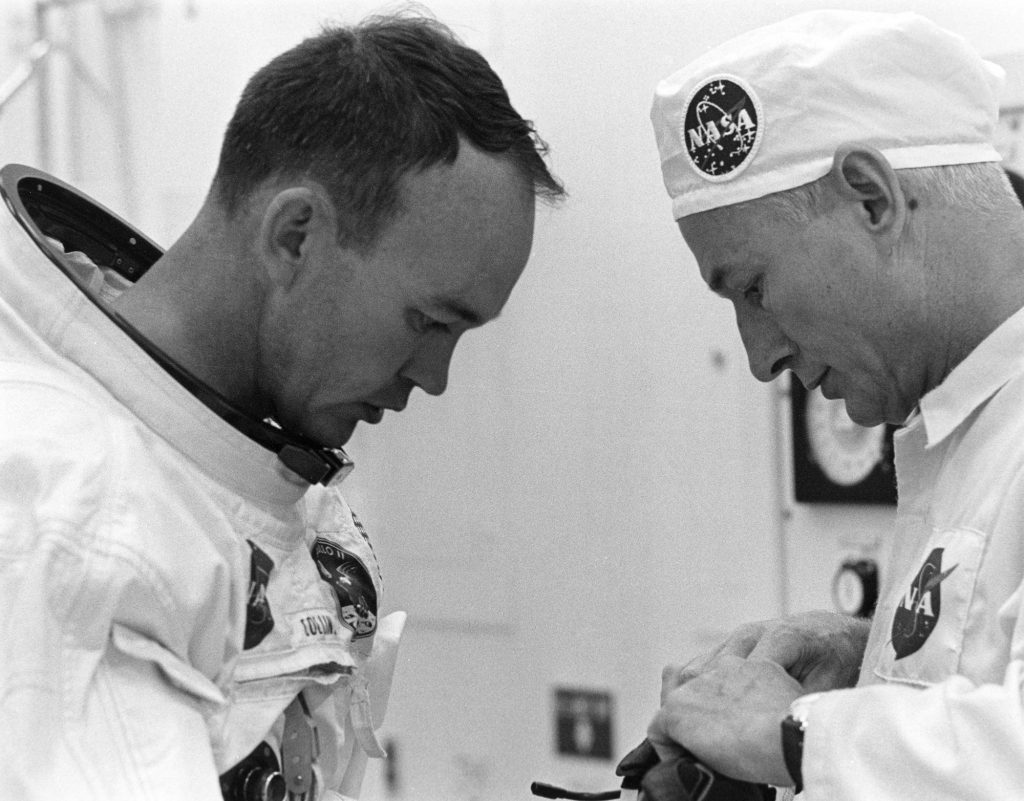Michael Collins is helped by suit tech Joe Schmitt while suiting up on July 16, 1969.