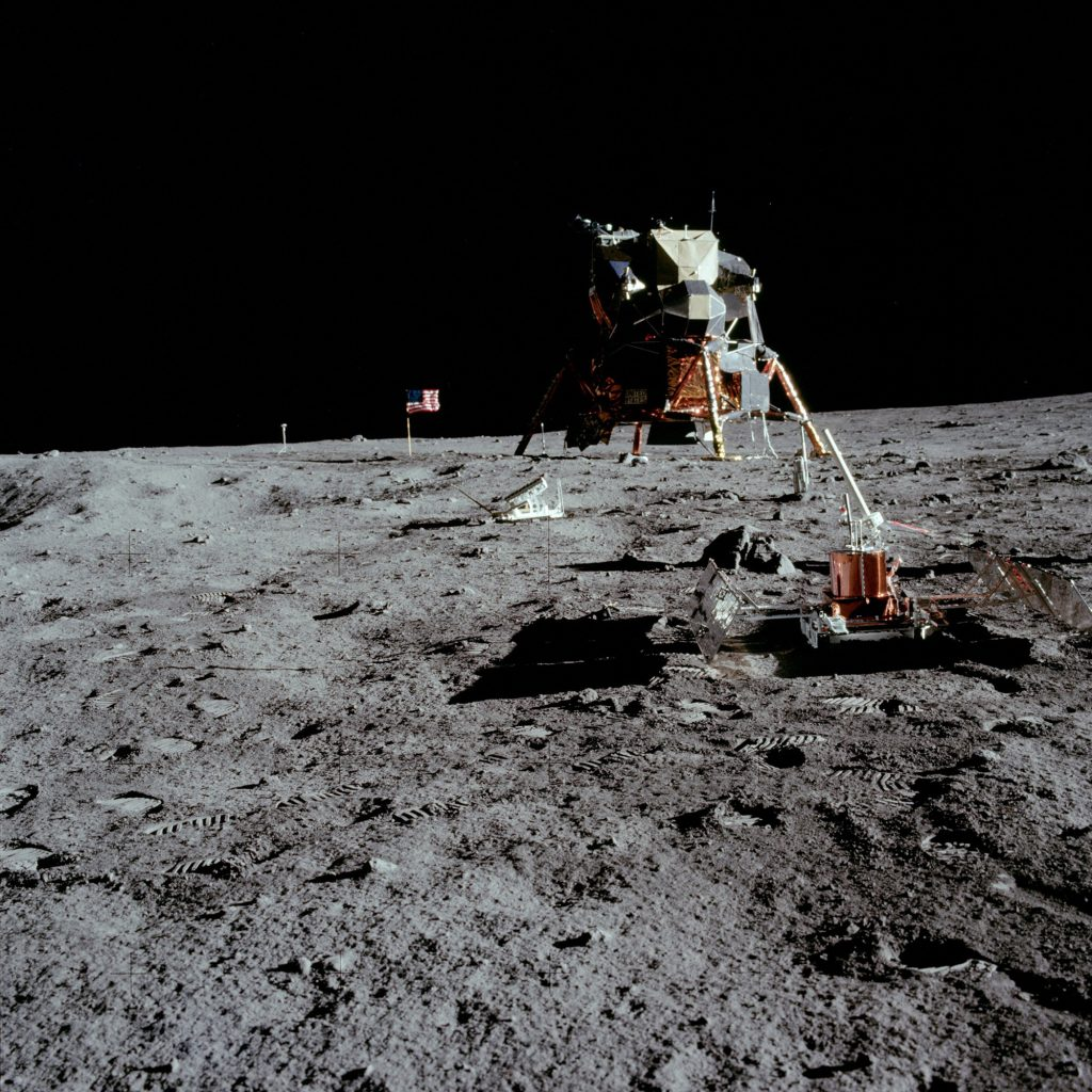 Resting on the lunar soil is a seismometer, part of the Early Apollo Scientific Experiments Package (EASEP). The Lunar Module and American flag can be seen in the distance.
