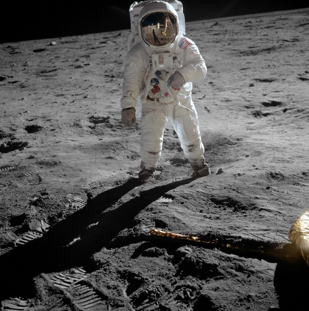 Edwin 'Buzz' Aldrin walks on the lunar surface. The plexiglass of his helmet reflects back the scene in front of him, including Neil Armstrong taking his picture.