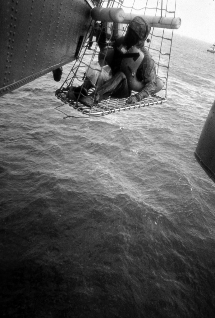 An unidentified crew member is hoisted aboard the recovery helicoptor for transport back to USS Hornet.