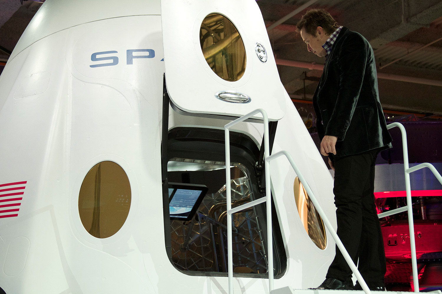SpaceX founder Elon Musk gives a peek inside the next generation Dragon space capsule during a media event to reveal the new design. The Dragon V2 will be the first man-rated spacecraft from the private company. Credit: Brenden Clark