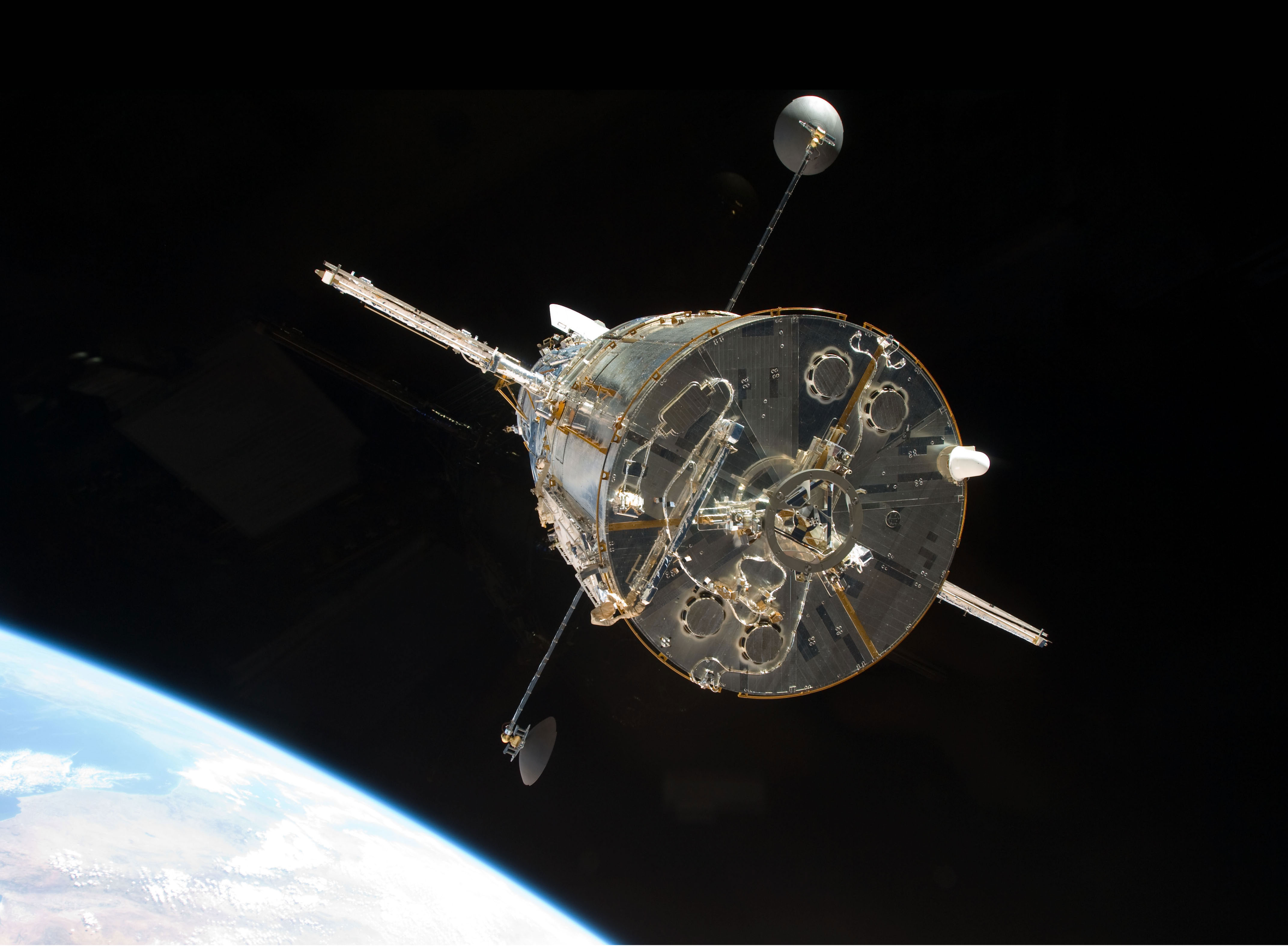 The Space Shuttle Atlantis moves away from Hubble after the telescope's release on May 19, 2009 concluded Servicing Mission 4. The Soft Capture Mechanism, a ring that a future robotic mission can grapple in order to de-orbit the telescope, is visible in the center. Credit: NASA