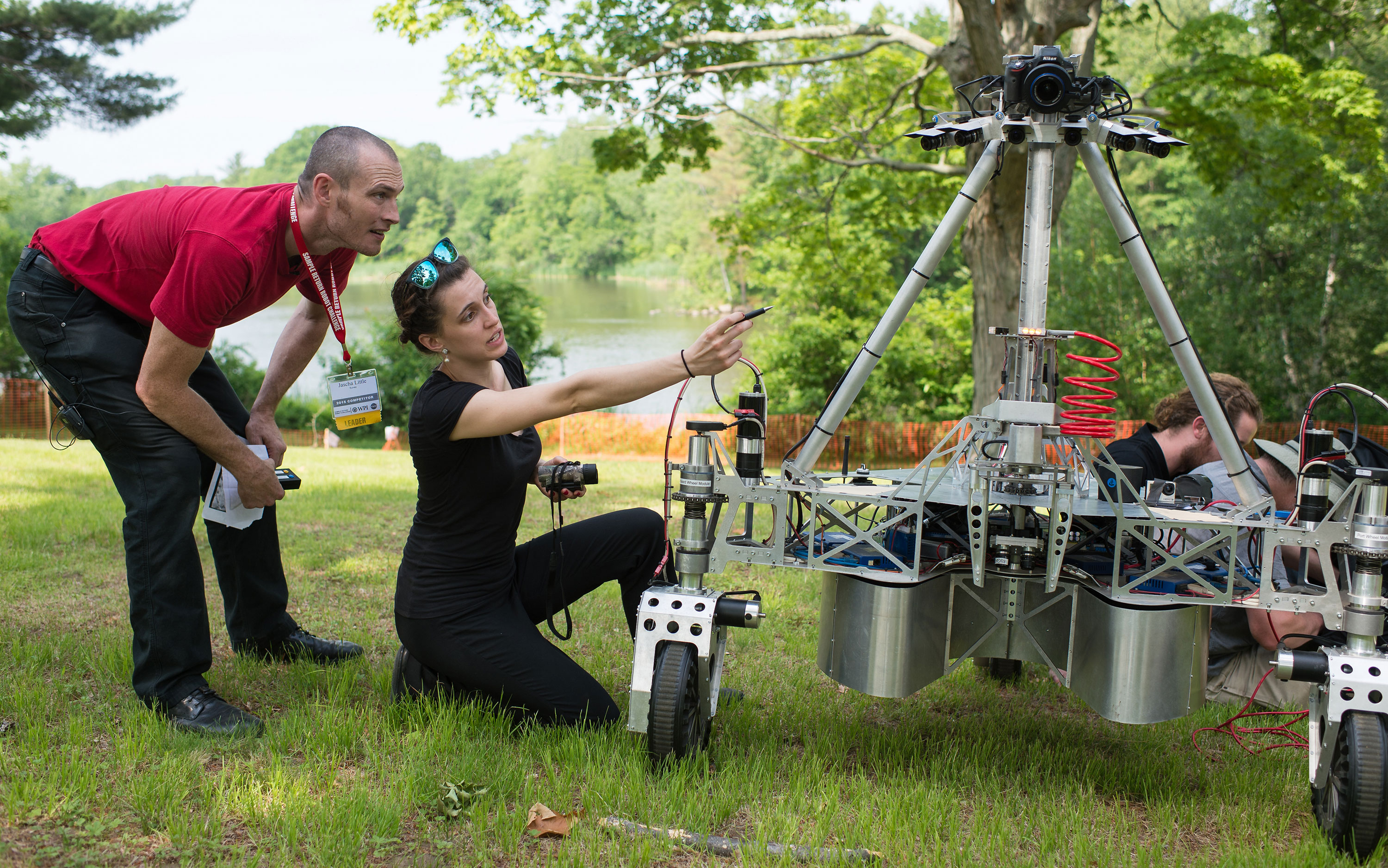 Jascha Little, left, and Zoe Stephenson of team Survey are seen with their robot during a communications update period during their attempt at the level two challenge at the 2015 Sample Return Robot Challenge. Credit: NASA/Joel Kowsky