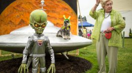 """Sue Morris and her dog """"Pepper"""" are seen with a model of a spacecraft and alien used for photos during the Mars New Year's celebration Saturday, June 20, 2015, in Mars, Pennsylvania. Credit: NASA/Bill Ingalls"""