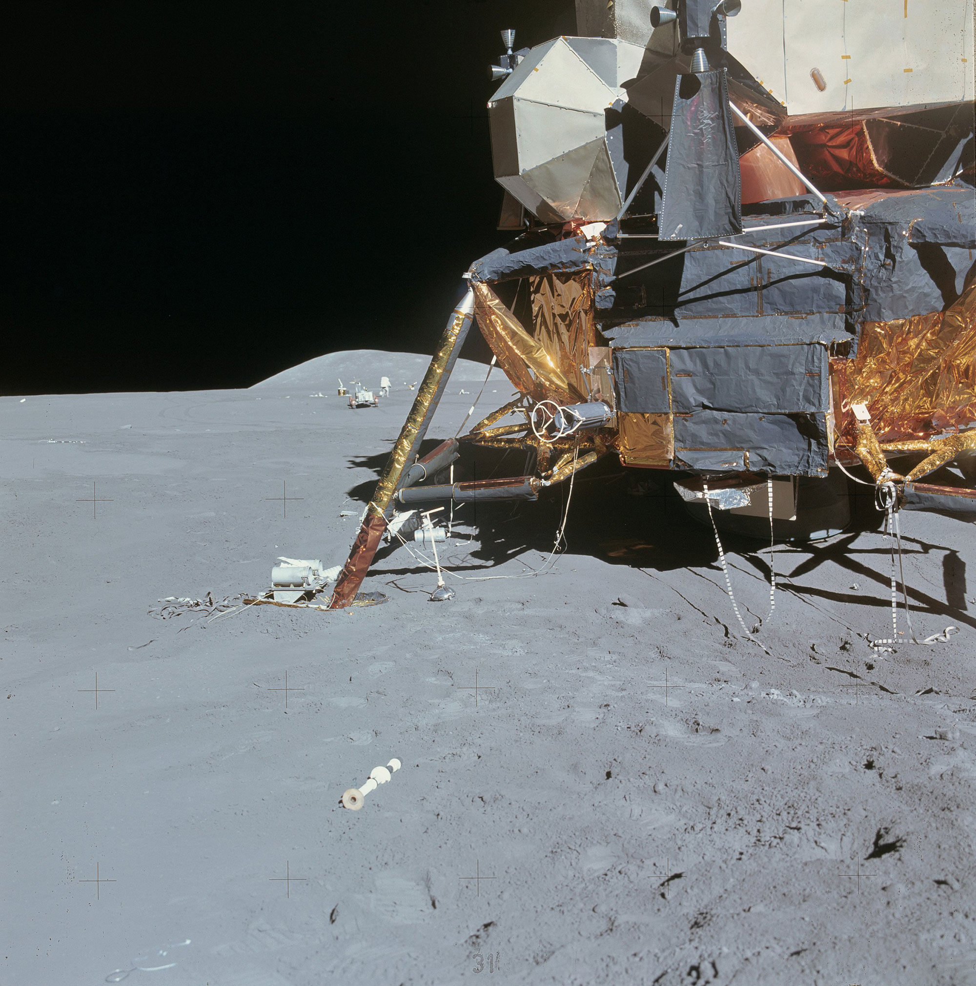 Lunar Module Falcon with the Lunar Rover seen behind its left side off in the distance. Credit: NASA via Retro Space Images