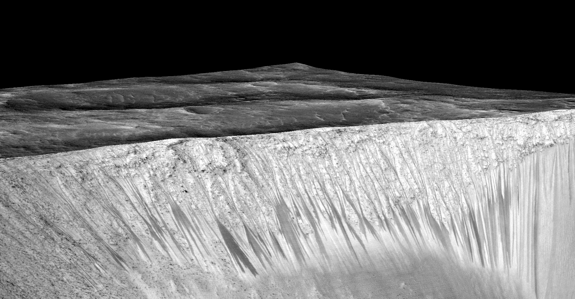 Dark narrow streaks called recurring slope lineae emanating out of the walls of Garni crater on Mars. The dark streaks here are up to few hundred meters in length. They are hypothesized to be formed by flow of briny liquid water on Mars. Credit: NASA/JPL/University of Arizona