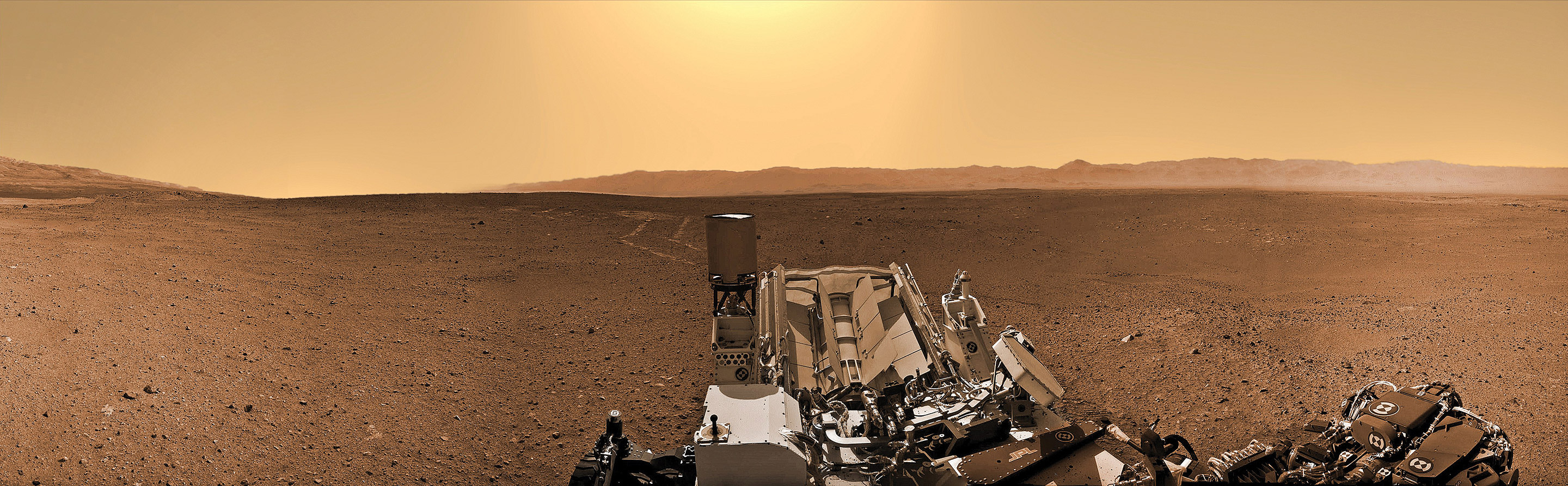 Curiosity looks back to her rover tracks, the foothills of Mount Sharp and the eroded rim of Gale Crater in the distant horizon on Sol 24 (Aug. 30, 2012). The robot is taking the first radiation measurements from the surface to determine if future human explorers can live on Mars. Featured on PBS NOVA TV. Credit: NASA/JPL-Caltech/Ken Kremer/Marco Di Lorenzo