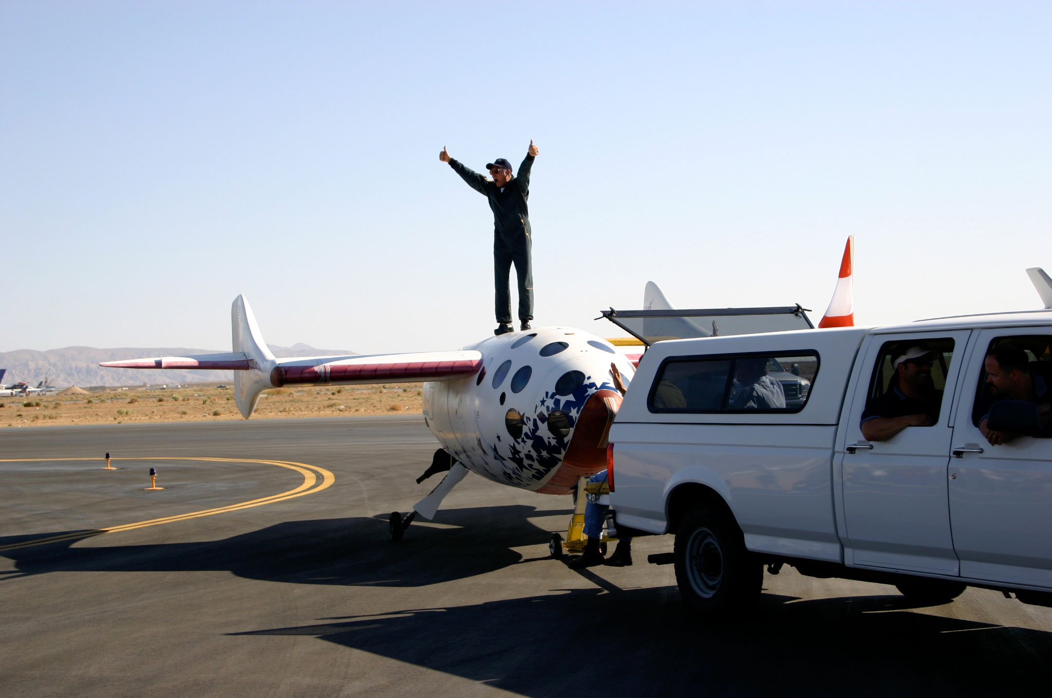 Mike Melvill celebrates atop SpaceShipOne after completion of his first of two trips to outer space aboard the vehicle.  Credit: http://www.flickr.com/photos/densaer/