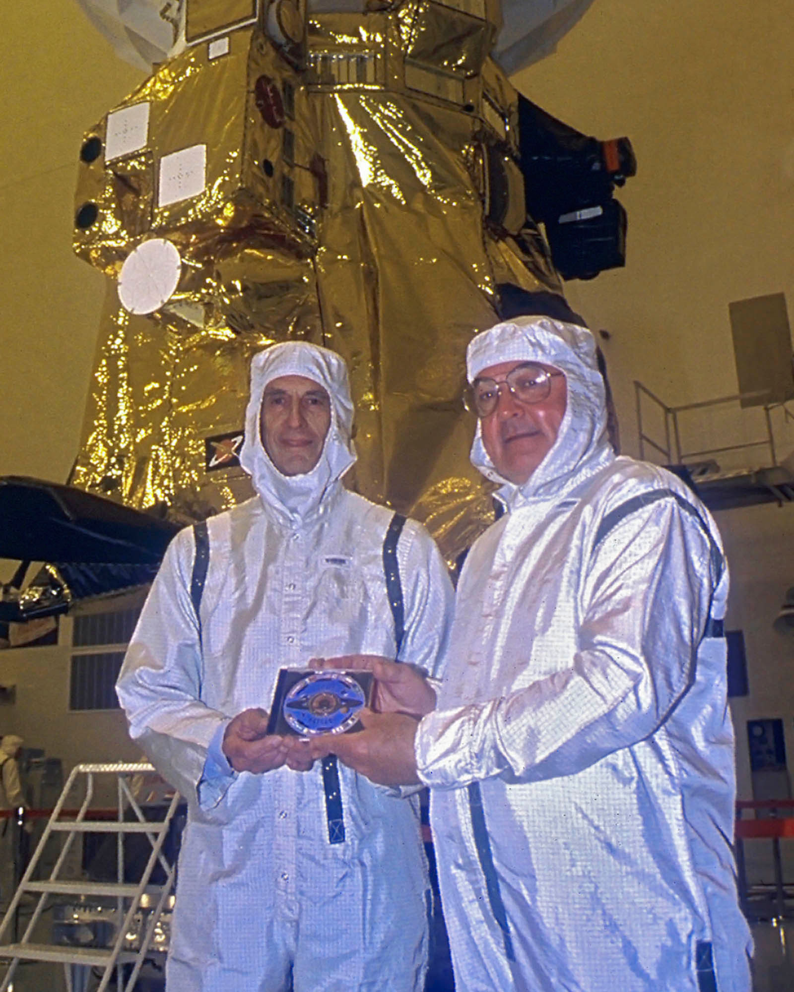 In the Payload Hazardous Servicing Facility at the Kennedy Space Centre Kohlhase (left) and Cassini Programme Manager, Richard Spehalski, hold the DVD containing 616,400 digitized signatures of people from 81 countries which was sent to Saturn on board Cassini, seen behind them. Charley designed the disk with the flags of 28 nations and symbolic golden eagle wing feathers. Credit: NASA/JPL
