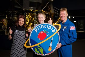 BBC presenter Lindsay Russel, logo designer Troy and Tim Peake with the Principia mission logo. The BBC's Blue Peter programme asked schoolchildren to design a mission patch for Tim and received more than 3000 entries.  Credit: ESA