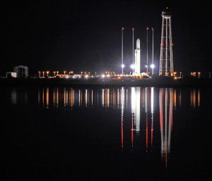 An Antares rocket stands erect, reflecting off the calm waters the night before its first night launch from NASA's Wallops Flight Facility, VA. Credit: Ken Kremer