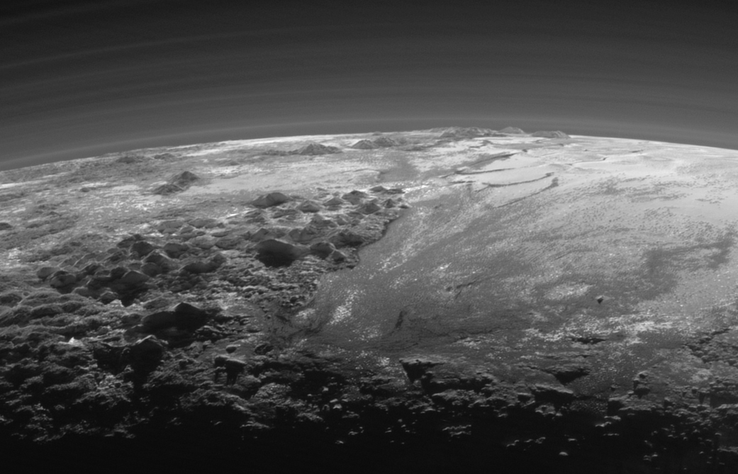 Figure 15: View looking back through Pluto's atmosphere towards the Sun, shortly after New Horizons' closest approach, showing the delicate structure and multiple haze layers of Pluto's atmosphere. To the left foreground and on the horizon are, respectively, the icy mountains of Norgay Montes and Hillary Montes, named for the first conquerors of Mount Everest. The smooth expanse of Sputnik Planum is to the right. Credit: NASA/JHUAPL/SwRI