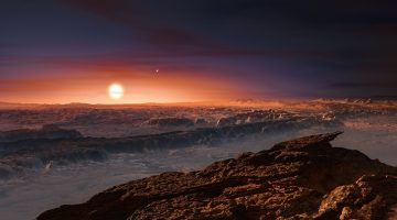 This artist's impression shows a view of the surface of the planet Proxima b orbiting the red dwarf star Proxima Centauri, the closest star to the Solar System. Proxima b orbits in the habitable zone where the temperature is suitable for liquid water to exist on its surface. Credit: ESO/M. Kornmesser